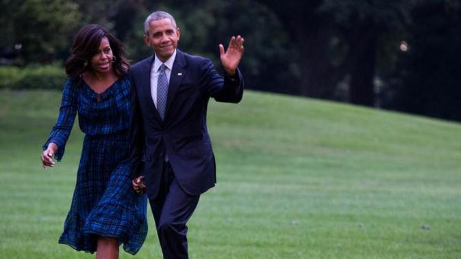 Presiden Amerika Serikat (AS) ke-44, Barack Obama menggandeng tangan sang istri, Michelle Obama, sambil menyapa awak media saat berjalan di halaman sisi selatan Gedung Putih di Washington, 28 September 2016. (AFP PHOTO / ZACH GIBSON)