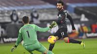Penyerang Liverpool, Mohamed Salah, mencetak gol ke gawang West Ham United pada laga Liga Inggris di Stadion London, Minggu (31/1/2021). Liverpool menang dengan skor 3-1. (Justin Setterfield/Pool via AP)