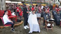 Presiden Joko Widodo disaksikan Ibu Negara Iriana saat mengikuti acara cukur rambut massal di Garut, Jawa Barat, Sabtu (19/1). Dalam acara cukur rambut massal ini, rambut Jokowi dicukur oleh tukang cukur langganannya, Herman. (Liputan6.com/Angga Yuniar)