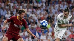 Gelandang Real Madrid, Gareth Bale (kanan) berebut bola dengan gelandang AS Roma Nicolo 'Zaniolo pada pertandingan Grup G Liga Champions di Stadion Santiago Bernabeu, Madrid, Spanyol, Rabu (19/9). Madrid membantai Roma 3-0. (AP Photo/Manu Fernandez)