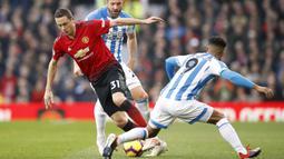 Gelandang Manchester United, Nemanja Matic, berusaha melewati pemain Huddersfield pada laga Premier League di Stadion Old Trafford, Rabu (26/12). Manchester United menang 3-1 atas Huddersfield. (AP/Martin Rickett)