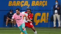 Bintang Barcelona Lionel Messi mencoba melewati pemain Girona Johan Mojica dalam pertandingan persahabatan pramusim di Stadion Johan Cruyff, Rabu (16/9/2020). (AP Photo/Joan Monfort)