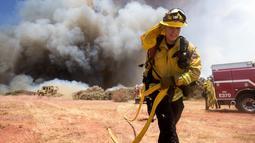 Petugas pemadam kebakaran berusaha memadamkan api di Cherry Valley, California (1/8/2020). Kebakaran lahan juga telah menjalar ke rumah penduduk. (AP Photo/Ringo H.W. Chiu)