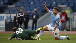 Striker Lazio, Ciro Immobile (kanan) berebut bola dengan gelandang Crotone, Jacopo Petriccione dalam laga lanjutan Liga Italia 2020/2021 pekan ke-27 di Olimpico Stadium, Roma, Jumat (12/3/2021). Lazio menang 3-2 atas Crotone. (AP/Alessandra Tarantino)