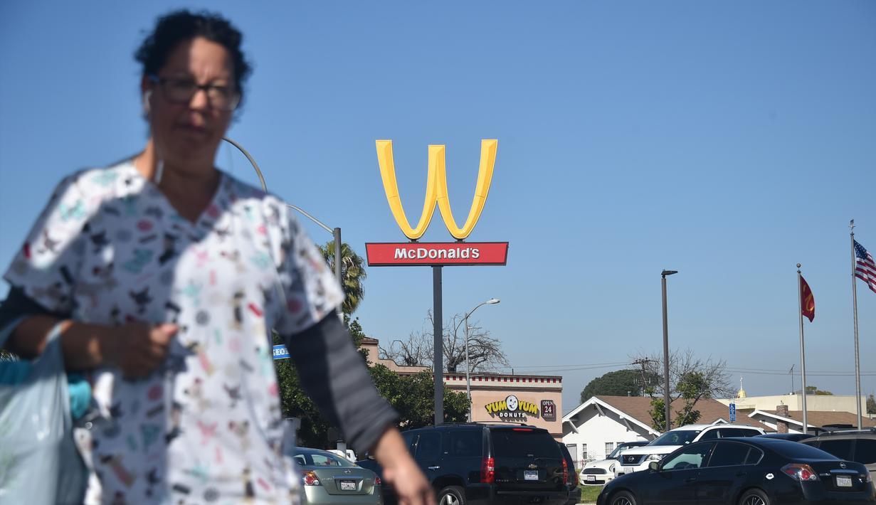 Seorang wanita berjalan dengan latar belakang plang logo restoran cepat saji McDonald's yang terbalik di Lynwood, California (8/3). Huruf W tersebut merupakan inisial untuk women atau wanita. (AFP Photo/Frederic J. Brown)
