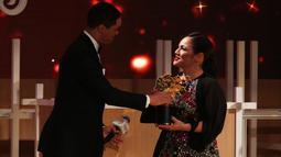 Guru sekolah Inggris, Andria Zafirakou menerima trofi Global Teacher Prize dari komedian Trevor Noah pada acara penganugerahan di Dubai, Minggu (18/3). Untuk itu Andria Zafirakou mendapatkan uang US $ 1 juta atau hampir Rp 14 miliar. (AP/Jon Gambrell)