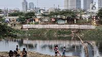 Anak-anak bermain di bantaran Kanal Banjir Barat dengan latar belakang gedung pencakar langit di Jakarta, Kamis (6/8/2020). Badan Pusat Statistik mencatat pertumbuhan ekonomi Indonesia Kuartal II/2020 minus 5,32 persen akibat perlambatan sejak adanya pandemi COVID-19. (merdeka.com/Iqbal S. Nugroho)