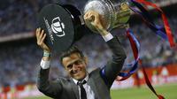 Pelatih FC Barcelona, Luis Enrique, membawa tropi Piala Raja Spanyol (Copa del Rey) di stadion Vicente Calderon, Spanyol, Minggu (28/5). Enrique mengaku bahagia bisa mempersembahkan satu trofi untuk Barca pada musim ini. (AP Photo)