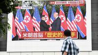 Pejalan kaki melihat layar yang menampilkan pertemuan antara pemimpin Korea Utara Kim Jong-un dan Presiden AS Donald Trump di Tokyo, Selasa (12/6). Untuk pertama kalinya dalam sejarah, Donald Trump dan Kim Jong-un bertemu. (AFP PHOTO/Martin BUREAU)