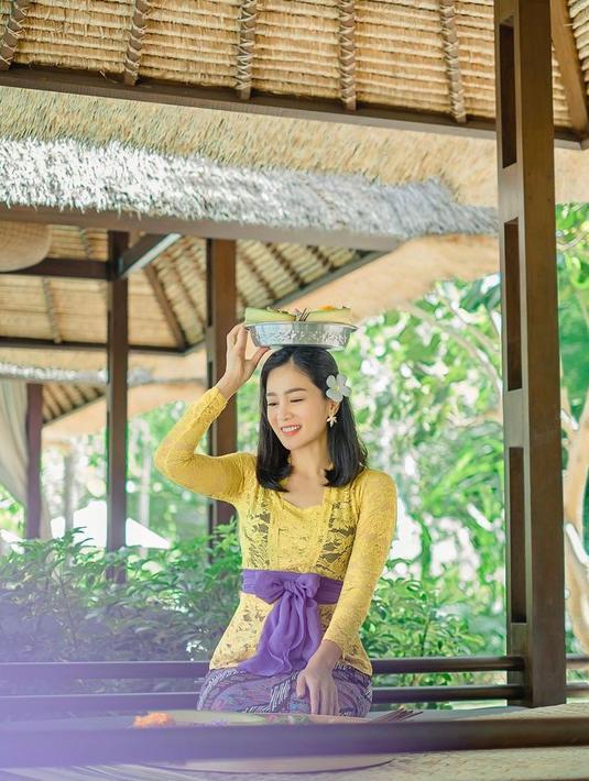 Bunga Zainal tampil cantik menawan dalam balutan kebaya Bali warna kuning dan ungu. Bunga kamboja yang diselipkan pada telinganya membuatnya terlihat lebih anggun. (Instagram/bungazainal05).
