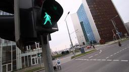 Lampu lalu lintas khusus pejalan kaki yang menampilkan simbol wanita di Vilnius, Lituania, Jumat (2/11). Hal itu untuk merayakan ulang tahun ke-100 wanita memperoleh pengakuan internasional dalam pemungutan suara di negara baltik. (Petras Malukas/AFP)