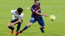 Pemain Valencia, Jose Gaya berebut bola dengan pemain Levante, Jorge Miramon  pada pertandingan La Liga Spanyol di Stadion Mestalla di Valencia, Spanyol, Minggu, (13/9/2020). Valencia menang telak 4-2. (AP Photo/Alberto Saiz)