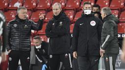 Manajer Sheffield United, Chris Wilder (kiri), dan Manajer Mancheseter United, Ole Gunnar Solskjaer (kanan) terlibat adu mulut dalam laga lanjutan Liga Inggris pekan ke-13 di Bramall Lane, Sheffield, Kamis (17/12/2020). Sheffield United kalah 2-3 dari Manchester United. (AFP/Peter Powell/Pool)