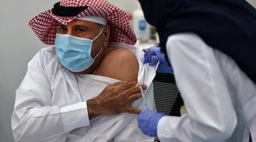 Warga sipil pertama saat menjalani penyuntikan vaksin Covid-19 di pusat vaksinasi yang diawasi Kementerian Kesehatan Arab Saudi di Riyadh, Arab Saudi, Kamis (17/12/2020). Arab Saudi akhirnya memulai vaksinasi Covid-19 setelah menerima dua pengiriman vaksin Pfizer-BioNTech. (AFP/Fayez Nureldine)