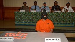Mohd Husaini Jaslee berserta barang bukti diperlihatkan saat konferensi pers menyusul penahanannya di kantor pabean di Bandara Ngurah Rai, Denpasar (4/10). Jaslee ditangkap setelah membawah pil ekstasi di dalam tas laptopnya. (AFP Photo/Sonny Tumbelaka)