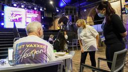 Pekerja Layanan Kesehatan Nasional menjawab pertanyaan di pusat vaksinasi Covid yang didirikan di klub malam Heaven di London, Minggu (8/8/2021). Heaven menjadi klub malam pertama di Inggris yang diubah sebagai pop-up pusat vaksinasi untuk mengajak kaum muda agar mau divaksin (AP/Alberto Pezzali)
