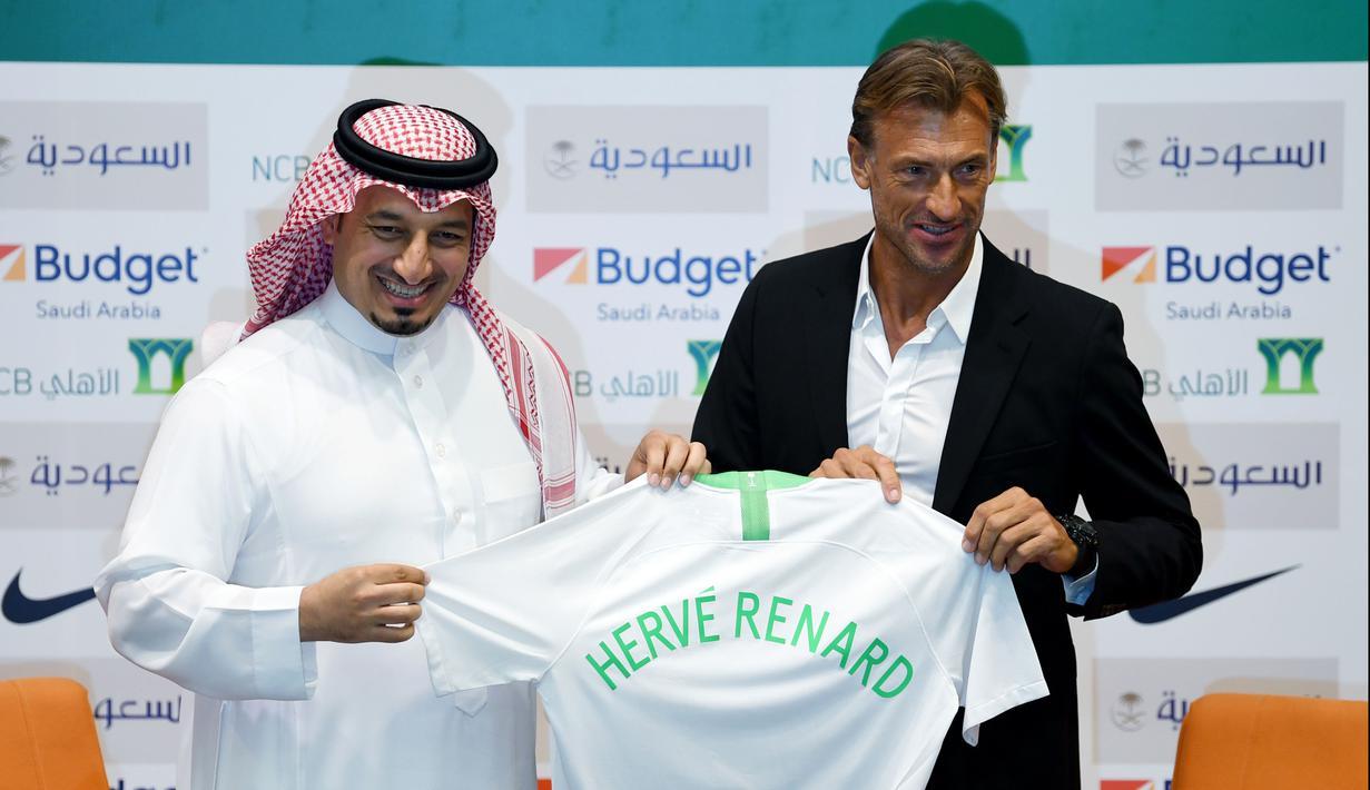 Pelatih asal Prancis, Herve Renard (kanan) dan ketua Federasi Sepakbola Saudi Yasser Almisehal (kiri) berpose dengan jersey Arab Saudi dengan nama dirinya di Jeddah (5/8/2019). Renard resmi menangani timnas Arab Saudi usai mundur dari kursi kepelatihan Maroko. (AFP Photo/Amer Hilabi)