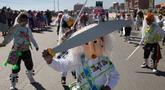 """Siswa mengenakan topeng dari wadah minyak goreng plastik sambil menari """"Paquchi"""" pada festival di Bolivia, Selasa (14/8). Siswa sekolah San Roque membuat kostum dari bahan daur ulang untuk meningkatkan kesadaran pengelolaan limbah padat. (AP/Juan Karita)"""