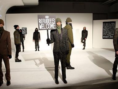 Sejumlah model berpose dengan poster #Refugees Welcome saat presentasi karya desainer Robert James dalam NYFW di New York, AS  (30/1). Presentasi ini menampilkan poster-poster yang menyindir kebijakan Donald Trump. (Robin Marchant Getty Images/AFP)