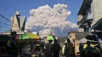 Orang-orang menyaksikan Gunung Sinabung memuntahkan material vulkanik saat meletus di Karo, Sumatera Utara, Selasa (2/3/2021).  Erupsi Gunung Sinabung juga mengendapkan abu di desa-desa terdekat. (AP Photo/Sugeng Nuryono)