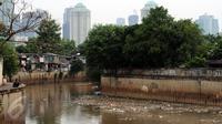 Ceceran sampah terlihat menggenang di Kali Krukut dekat TPU Karet Bivak Jakarta, Sabtu (5/11). Tampak bangunan semi permanen yang dijadikan pemukiman oleh warga di sisi Kali Krukut. (Liputan6.com/Helmi Fithriansyah)