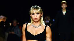 Miley Cyrus berjalan di catwalk untuk show Marc Jacobs Fall 2020 selama New York Fashion Week di New York City, Rabu (12/2/2020). Miley Cyrus memancarkan energi rockstar dalam balutan bralette hitam dipadu celana panjang dengan warna senada serta menenteng coat zebra (Slaven Vlasic/Getty Images/AFP)