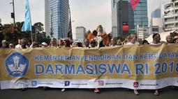 Ratusan mahasiswa internasional mengenakan pakaian adat Indonesia sambil membawa spanduk saat pawai kelulusan beasiswa Kemendikbud di car free day (CFD), Jakarta, Minggu (6/5). (Merdeka.com/Iqbal Nugroho)