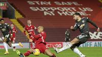 Bek Liverpool, Fabinho berusaha memblokir tembakan gelandang Manchester United, Bruno Fernandes pada pertandingan lanjutan Liga Inggris di Stadion Anfield, Senin (18/1/2021). Dengan hasil imbang ini, MU masih kokoh dipuncak klasemen. (Michael Regan/Pool via AP)