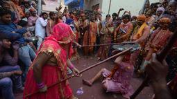 Pria saat dipukuli para wanita dengan tongkat (lathi) selama perayaan Lathmar Holi di Barsana di Mathura, India, (24/2). Lathmar Holi adalah perayaan lokal festival Hindu Holi, biasanya beberapa hari sebelum festival Holi. (AFP Photo/Dominique Faget)