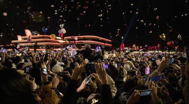 Orang-orang memakai masker wajah melepaskan balon selama hitung mundur Tahun Baru di Wuhan di provinsi Hubei tengah China (1/1/2021). Warga Wuhan memenuhi jalan-jalan merayakan Tahun Baru ketika seluruh dunia menderita di tengah penguncian Covid-19. (AFP/Noel Celis)