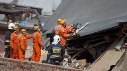 Petugas penyelamat mencari korban di reruntuhan sebuah apartemen tua yang ambruk di Swiebodzce, Polandia, Sabtu (8/4). Apartemen yang rubuh itu merupakan bangunan tua yang telah berdiri sebelum Perang Dunia II berlangsung. (Natalia DOBRYSZYCKA/AFP)