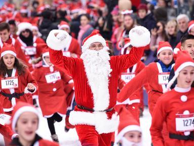 Orang-orang berpakaian seperti Sinterklas mengambil bagian dalam Santa Claus Run di Pristina, Kosovo, Minggu (16/12). Ratusan pelari berpartisipasi dalam lomba lari amal untuk menggalang dana bagi keluarga yang membutuhkan di Kosovo. (Armend NIMANI/AFP)