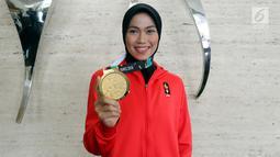 Atlet Taekwondo Defia Rosmaniar menunjukkan medali emas Asian Games 2018 saat berkunjung ke SCTV, Senayan City, Jakarta, Senin (20/8). Kunjungannya tersebut untuk melakukan wawancara. (Liputan6.com/Johan Tallo)