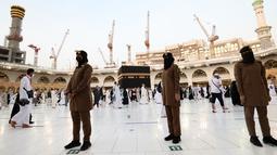 Para polisi wanita Saudi berjaga-jaga saat jemaah mengelilingi Ka'bah pada rangkaian ibadah haji di Masjidil Haram, Makkah, Selasa (20/7/2021). Kini, para personel perempuan bergabung dengan rekan-rekan pria mereka dalam menjaga kota suci selama musim haji. (Fayez Nureldine / AFP)