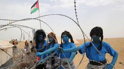 """Warga Palestina bergaya seperti karakter dari film """"Avatar"""" berpose selama protes menuntut hak untuk kembali ke kampung halaman mereka di perbatasan Israel-Gaza, Timur Khan Yunis di Gaza selatan Strip, (4/5). (AFP Photo/Said Khatib)"""