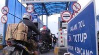 Pengendara motor saat antre di pintu tol Jembatan Suramadu sisi Surabaya, Jumat (15/1). Petugas pintu tol beberapa kali terpaksa menutup akses untuk motor, karena angin bertiup sangat kencang.(Antara)