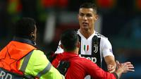 Seorang fans Mancheter United berlari menghampiri penyerang Juventus, Cristiano Ronaldo usai pertandingan grup H Liga Champions di Trafford, Inggris (23/10). Juventus mengalahkan MU dengan skor 1-0 berkat gol Paulo Dybala. (AP Photo/Dave Thompson)