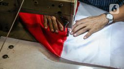 Pekerja menjahit bendera merah putih di kiosnya, kawasan Pasar Senen, Jakarta, Rabu (5/8/2020). Menjelang peringatan HUT ke-75 Kemerdekaan RI, sejumlah pedagang mengaku penjualan pernak-pernik bendera merah putih menurun 50 persen dibanding tahun lalu akibat COVID-19. (Liputan6.com/Faizal Fanani)