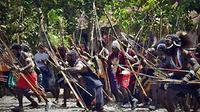 Puluhan orang membawa panah saat akan melaksanakan ritual adat kremasi jenazah korban perang suku di Timika, Papua, Senin (18/1). (Antara)