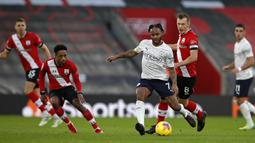 Gelandang Manchester City, Raheem Sterling (kanan), melepaskan umpan dalam laga lanjutan Liga Inggris pekan ke-14 melawan Southampton di St. Mary's Stadium, Southampton, Sabtu (19/12/2020). Manchester City menang 1-0 atas Southampton. (AFP/Paul Childs/Pool)
