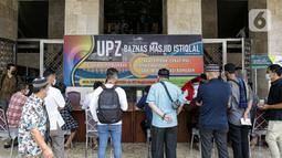 Umat muslim antre membayar zakat fitrah kepada amil zakat di Masjid Istiqlal, Jakarta, Jumat (7/5/2021). Panitia Zakat Masjid Istiqlal mulai membuka layanan pembayaran zakat fitrah dengan pembayaran senilai Rp 50 ribu atau 3,5 liter beras. (Liputan6.com/Faizal Fanani)