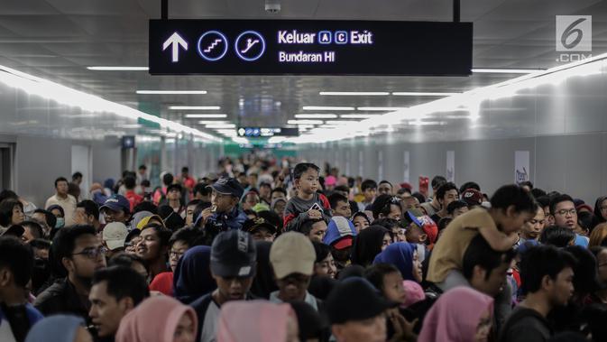 Warga mengantre untuk menaiki kereta MRT di pintu masuk Stasiun MRT Bundaran HI, Jakarta, Minggu (24/3). Moda Raya Terpadu (MRT) Jakarta Fase 1 dengan rute Bundaran HI - Lebak Bulus resmi beroperasi. (Liputan6.com/Faizal Fanani)