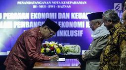 Gubernur Bank Indonesia (BI) Agus Martowardoyo menandatangani nota kesepahaman (Mou) dengan MUI, Baznas, dan BWI di Gedung MUI, Jakarta, Rabu (24/1). (Liputan6.com/Faizal Fanani)