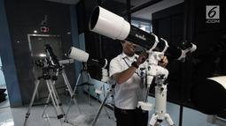 Petugas mempersiapkan teleskop yang akan digunakan untuk melihat fenomena Supermoon di Planetarium Jakarta, Selasa (30/1). Planetarium Jakarta menggelar nonton bareng fenomena Supermoon dengan menyiapkan 16 teleskop. (Liputan6.com/Arya Manggala)