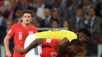 Pemain timnas Inggris, Raheem Sterling berebut bola dengan bek Kolombia, Yerry Mina pada babak 16 besar Piala Dunia 2018 di Stadion Spartak, Selasa (3/7). Sterling menjadi bahan pembicaraan setelah tertangkap kamera menggendong Mina (AFP/YURI CORTEZ)