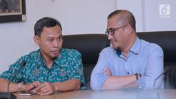 Komisioner KPU RI, Pramono Ubaid Tanthowi (kiri) berbincang dengan Ilham Saputra disela-sela penyampaian keterangan terkait putusan PTUN yang memenangkan gugatan PKPI di gedung KPU, Jakarta, Kamis (12/4). (Liputan6.com/Helmi Fithriansyah)