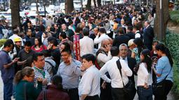 Orang-orang berkumpul diluar gedung di sepanjang Reforma Avenue setelah terjadi gempa di Mexico City, Meksiko (16/2). Pusat gempa berada di lokasi 37 kilometer timur laut Pinotepa de Don Luis, Oaxaca. (AP Photo/Marco Ugarte)