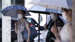 Warga mengenakan masker untuk mencegah penyebaran Covid-19 menggunakan payung di bawah sinar matahari di Tokyo (12/8/2020). Menurut Badan Meteorologi Jepang, cuaca panas telah ditetapkan dengan suhu naik lebih dari 34 derajat Celcius (93,2 derajat Fahrenheit) di Tokyo. (AP Photo/Eugene Hoshiko)