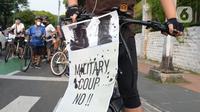 Peserta aksi SaveMyanmar menempelkan poster pada sepedanya di kawasan Bundaran HI, Jakarta, Sabtu (24/4/2021). Aksi ini bentuk kecaman atas kudeta ilegal dan menuntut militer Myanmar segera mengakhiri kekerasan serta mengembalikan demokrasi sesuai keinginan rakyat Myanmar. (merdeka.com/Imam Buhori)