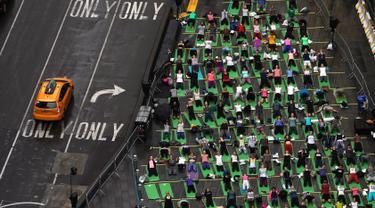 Ribuan orang berpartisipasi dalam yoga outdoor di kawasan Times Square, New York saat Summer Solstice atau hari dengan siang terpanjang di musim panas, Kamis (21/6). Acara itu menandai Hari Yoga Internasional yang jatuh pada 21 Juni (TIMOTHY A. CLARY/AFP)